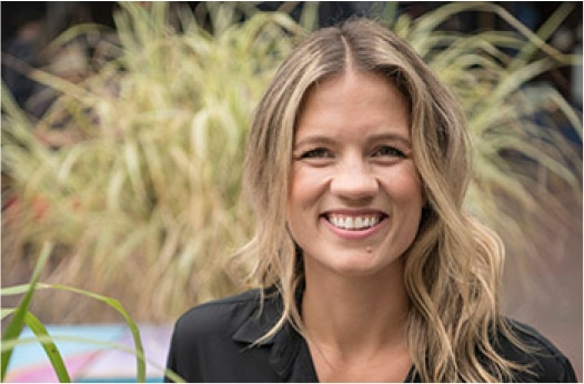 Claudia Richard, PR Communication Manager of Yulu, smiling on front of plants.