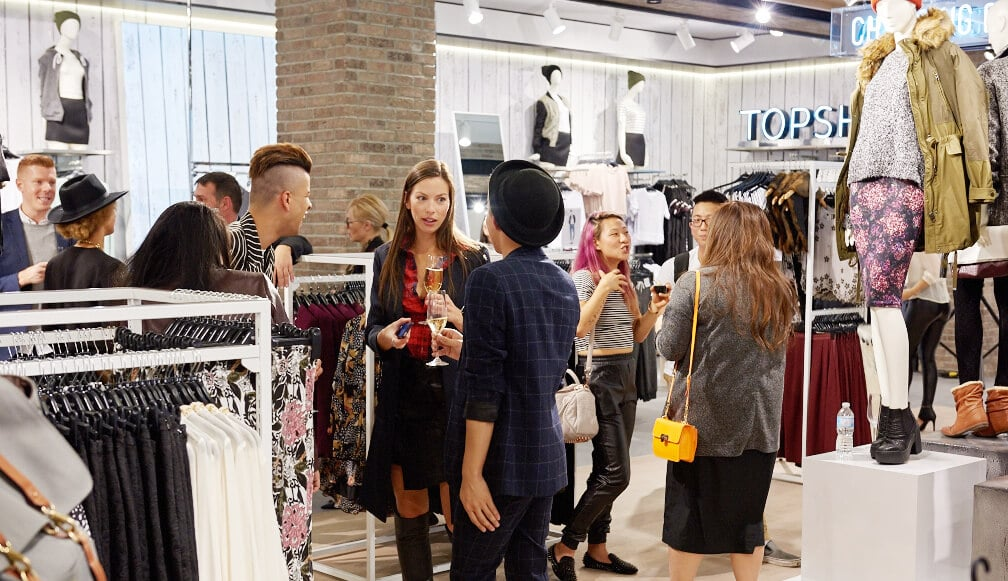 http://Group%20of%20influencers%20talking%20to%20one%20another%20in%20a%20Topshop%20store