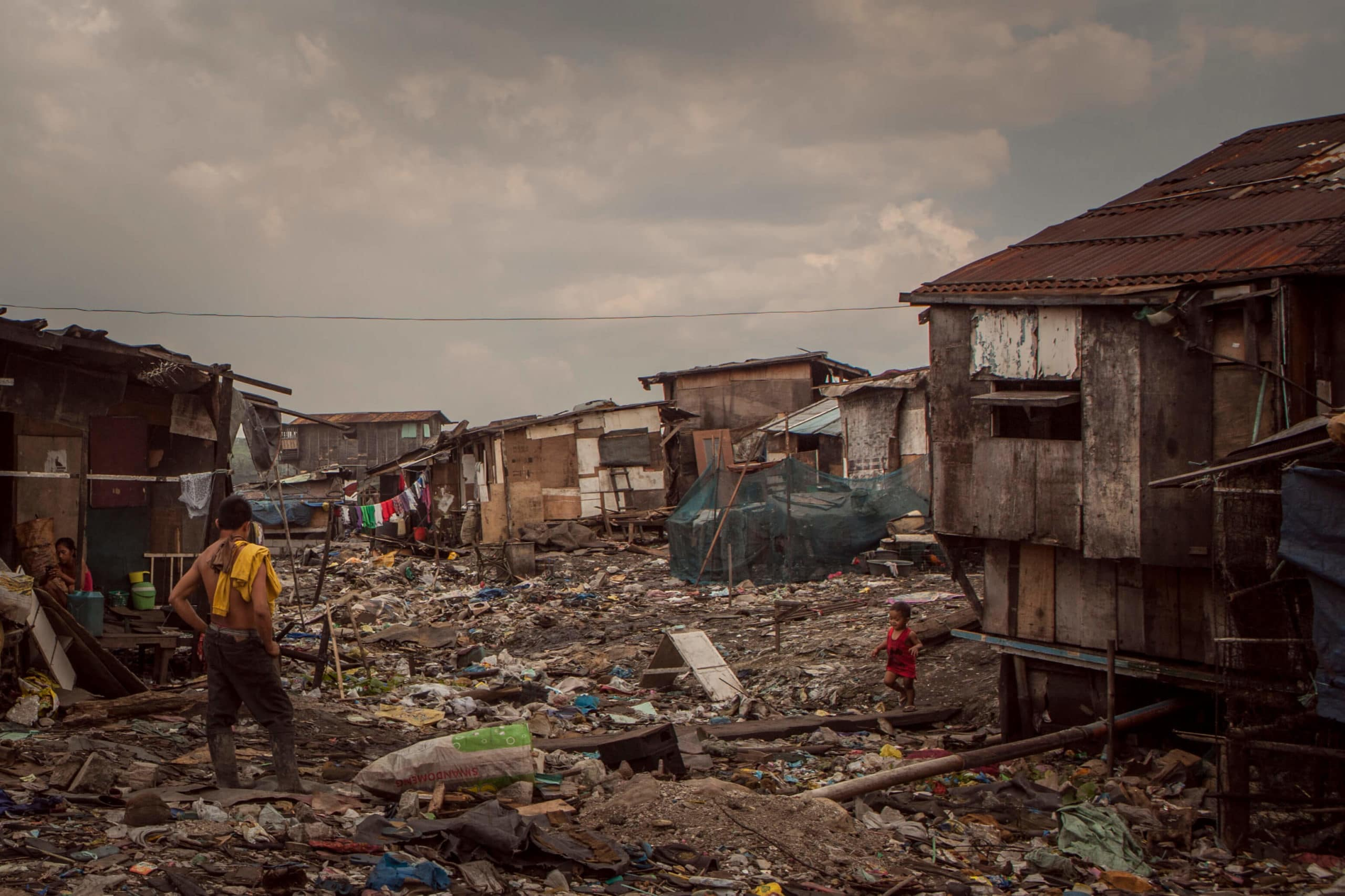 a photo of a slum in an east asian country. Trash is strewn everythwere, few people stand around.