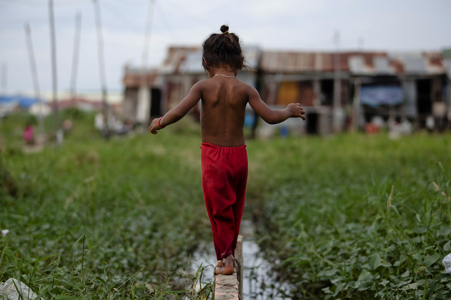 a small child walks along a water filled gutter, surrounded by green grass with a shabby house in the background.