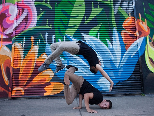 http://Two%20breakdancers%20in%20front%20of%20a%20mural%20of%20vibrant%20flowers