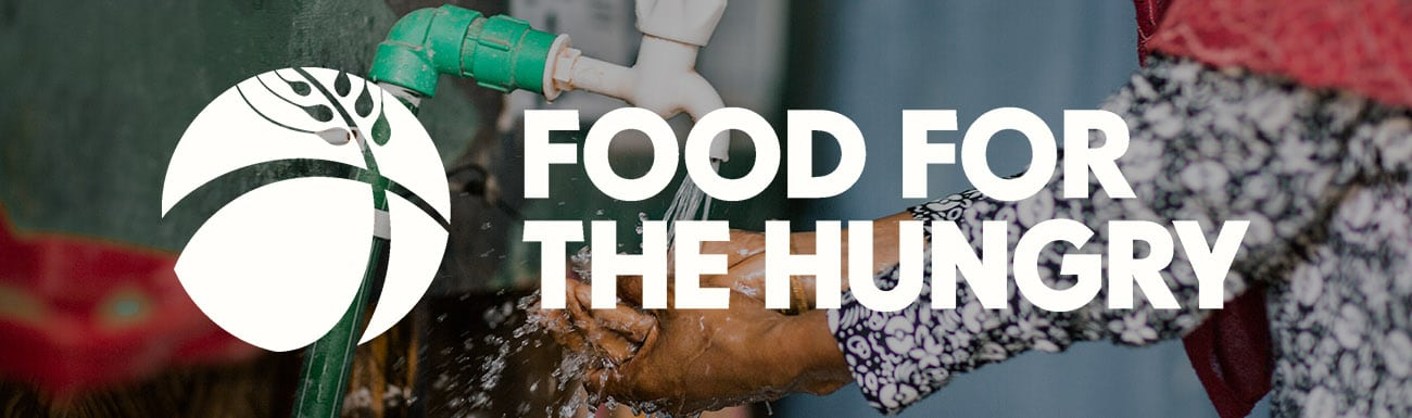 Food for the Hungry logo superimposed on a photo of a clsoeup of a child holding a hand