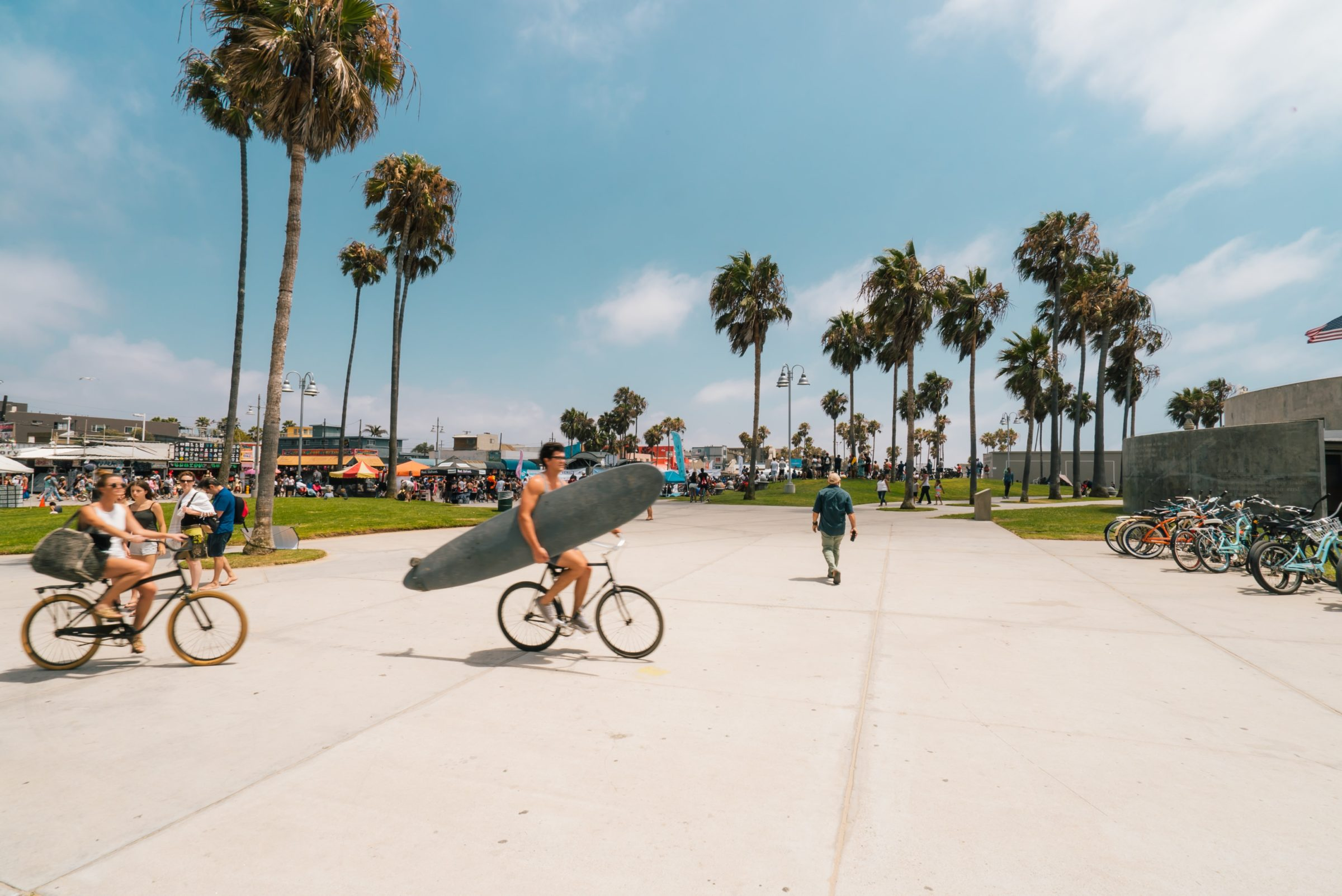 http://Man%20on%20a%20bike%20holding%20surfboard%20at%20the%20beach