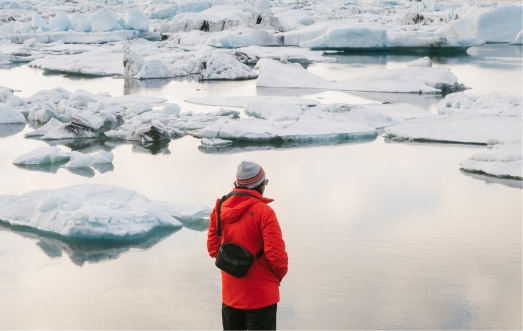 person with red jacket standing next to the icebergs