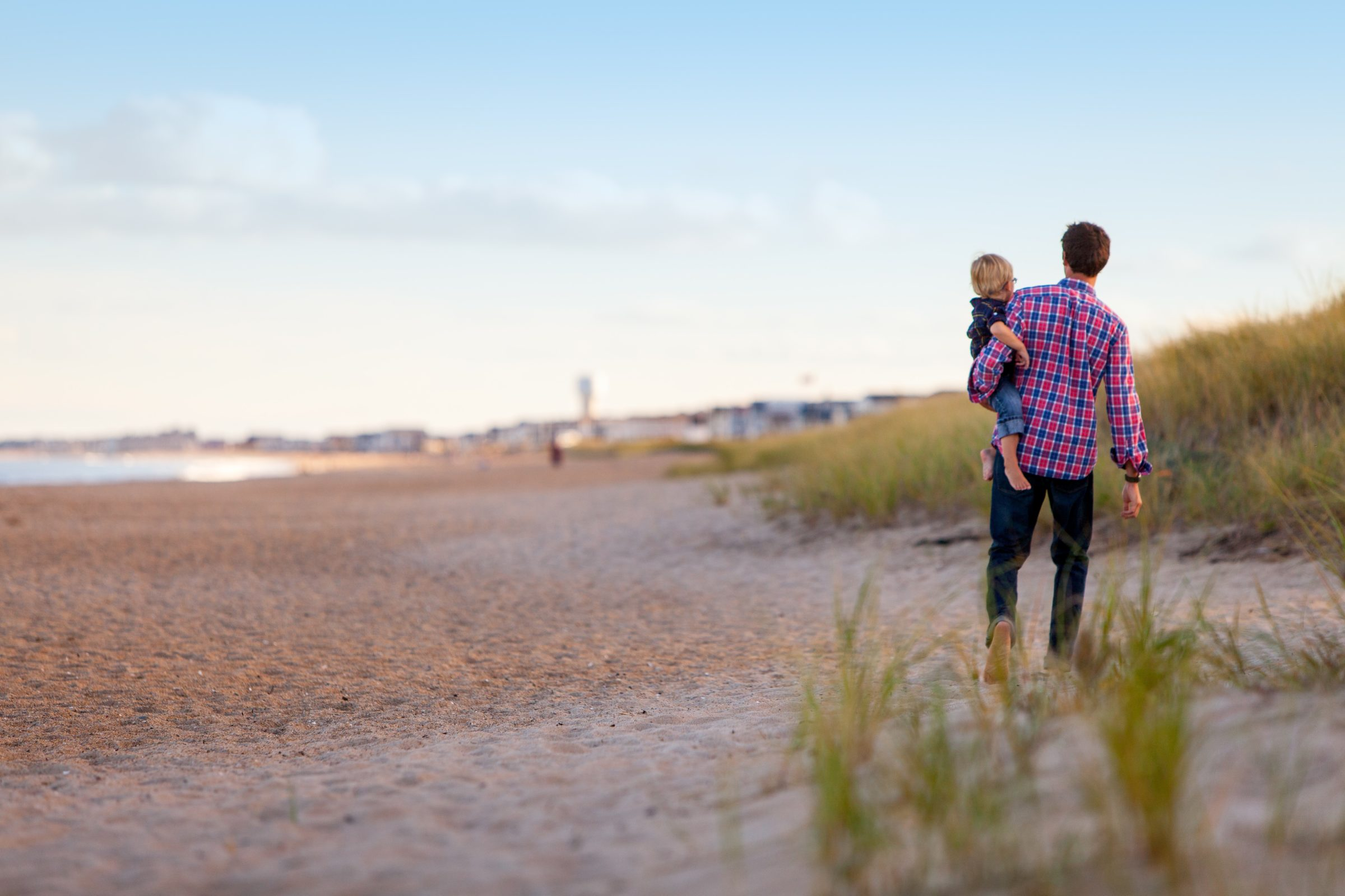 Man holding a young boy looking out at the beach