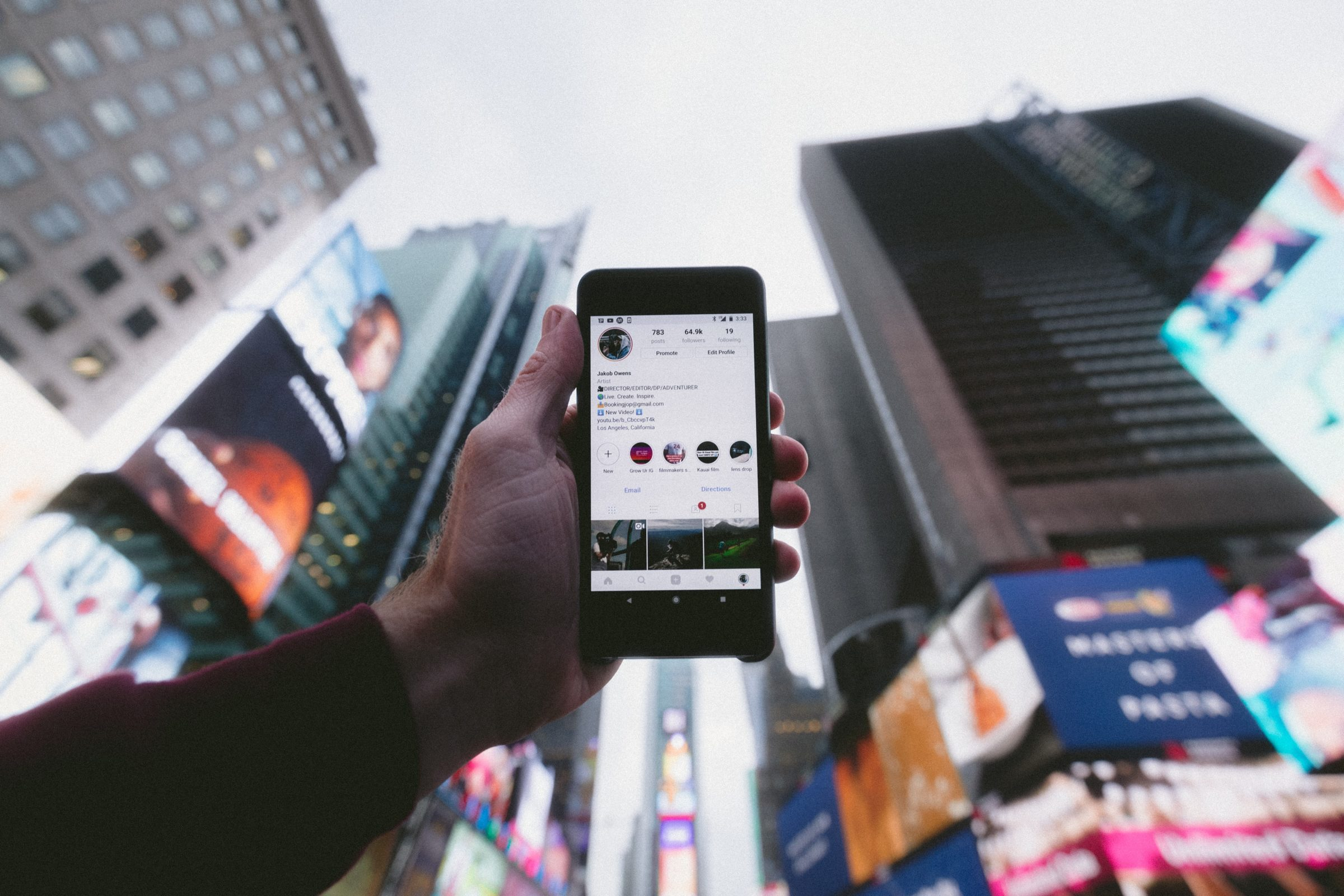 http://Person%20holding%20up%20a%20phone%20in%20front%20of%20city%20buildings