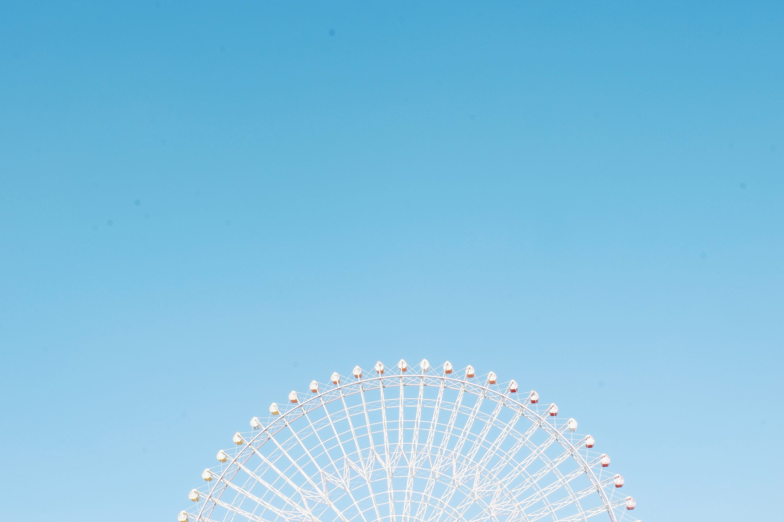 http://Top%20half%20of%20a%20white%20ferris%20wheel%20in%20front%20of%20a%20blue%20sky