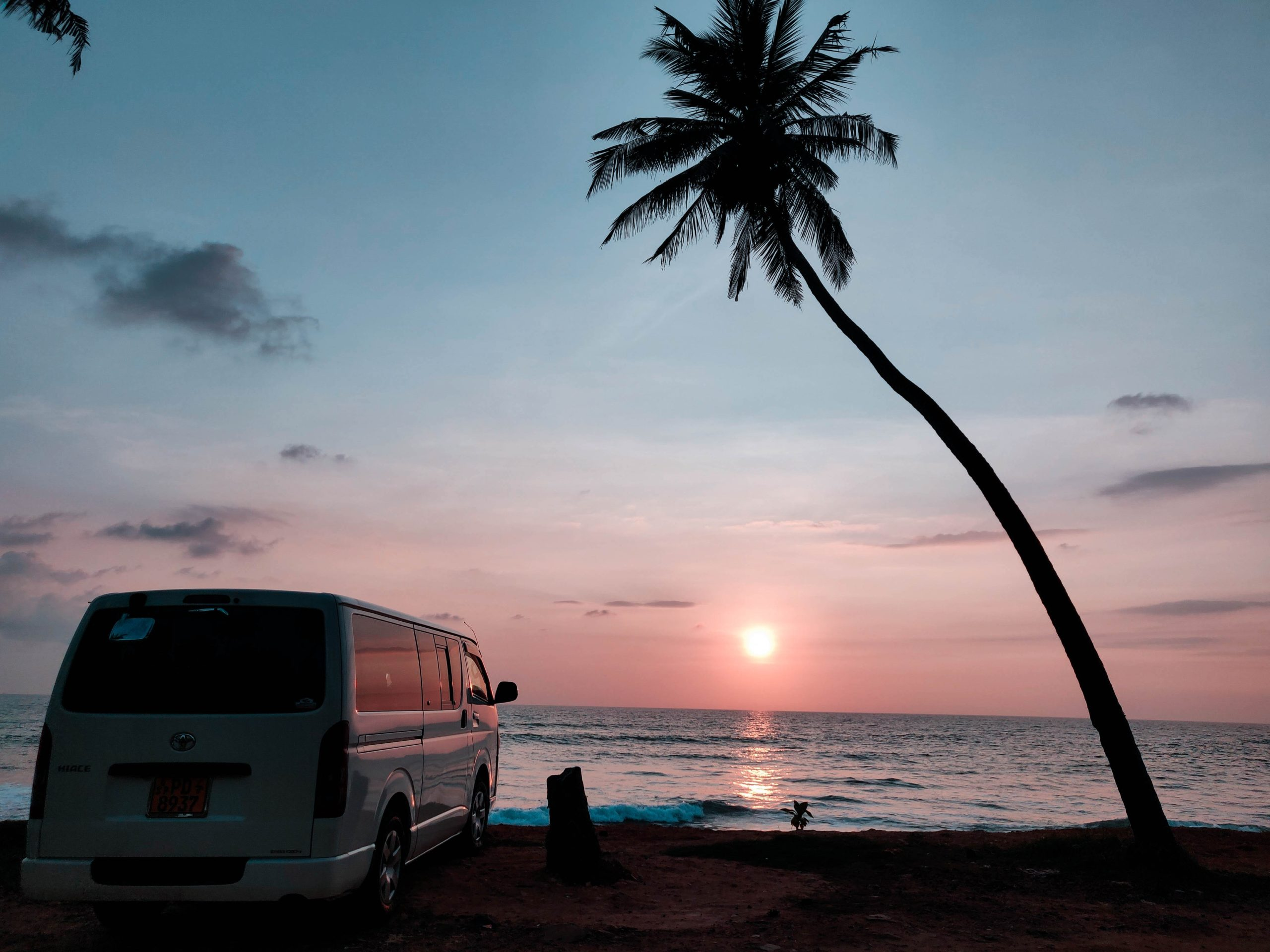 Parked van looking out at a beach sunset
